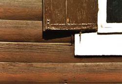 Rotbraunen Holzschutzanstrich der Rundbohlen auf der hofseitigen Fassade des Hauses