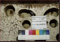 Zierbrett, EG, Westseite, Holzoberfläche stark verwittert, die vier Farbschichten stammen wahrscheinlich aus der 2. Hälfte des 20. Jahrhunderts